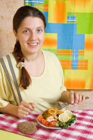 Young woman eating breaded fish in her kitchen Stock Photo - 9578610