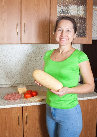 farci: Woman with food products for stuffed vegetable marrow. See in series stages of cooking of stuffed vegetable marrow