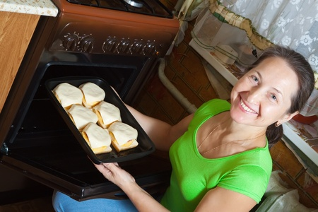Mature woman roasting stuffed vegetable marrow on pan in oven.