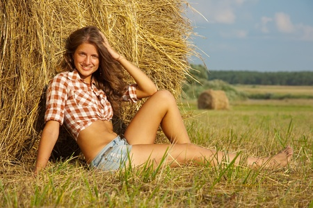 hay: Pretty girl in checked shirt resting on straw bale Stock Photo