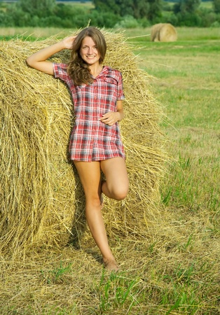 Pretty girl in checked dress resting on straw bale photo