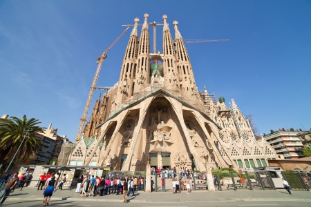 familia: BARCELONA, SPAIN - APRIL 12: Tourists looking Sagrada Familia in April 12, 2011 in Barcelona, Spain.  Expiatory Church of the Holy Family (Sagrada Familia) by Catalan architect Antoni Gaudi, building is begun in 1882 and completion is planned in 2030.