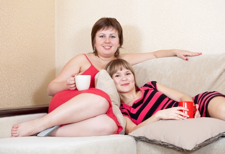 Two young women   having fun with cups of tea photo
