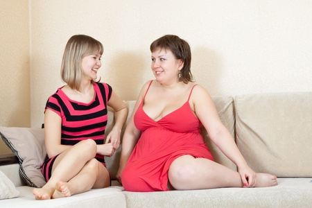 Two young women talking on sofa in home photo