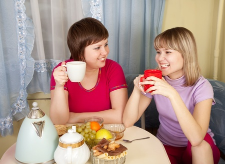 Girls  drinks tea and talking in the kitchen Stock Photo - 9578778