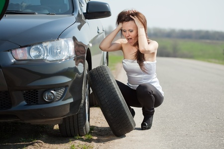 breakage: woman during the wheel changing at road