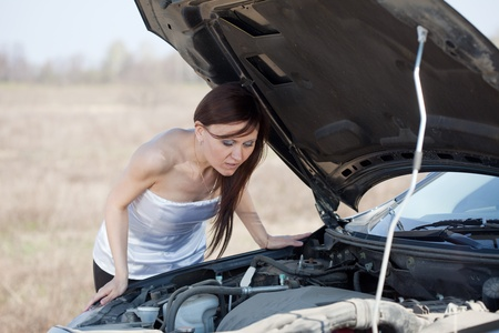 Mid adult woman repairing her car outdoor  photo