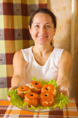 farci: Woman with cooked baked stuffed tomato. Focus on tomato. See in series stages of cooking of farci tomato  Stock Photo