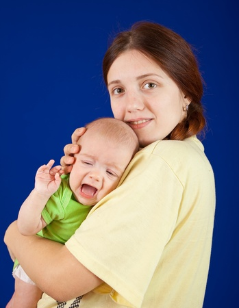 whining:  mother with her 3 month whining daughter over blue background