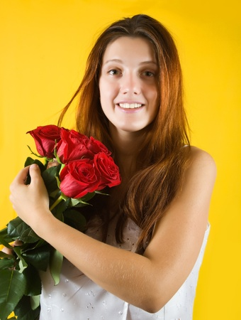 Portrait of tender girl with roses over yellow background photo