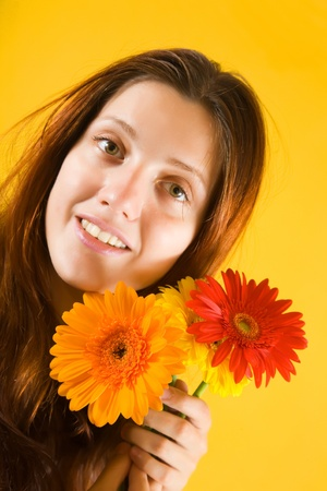 young girl with flowers on yellow background photo