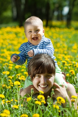 Happy mother and baby laying on dandelion meadow Stock Photo - 9663172
