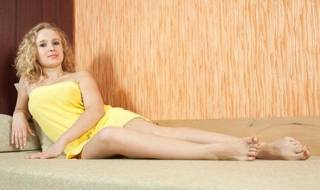 Sexy girl in yellow lying on sofa photo