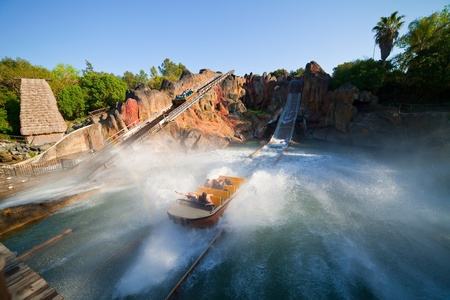 SALOU, SPAIN - APRIL 11: People riding in Theme Park in April 11, 2011 in Salou, Spain. Tutuki Splash is one of most exhilarating rides in Polynesian area  at Port Aventura