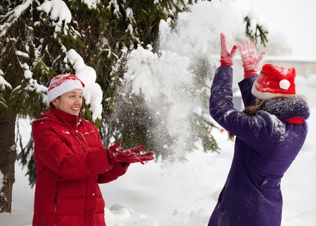 Two  young women throwing snow  in the air in park  photo