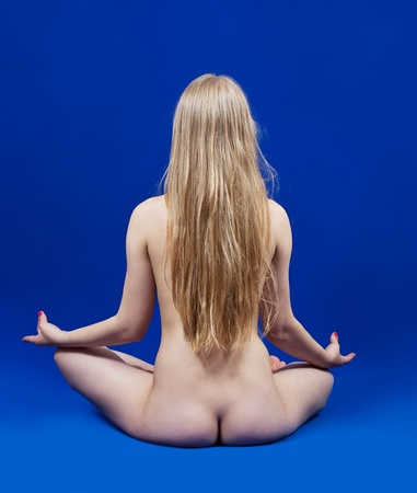 Rear view of nude girl practicing yoga over blue background Stock Photo - 9676089