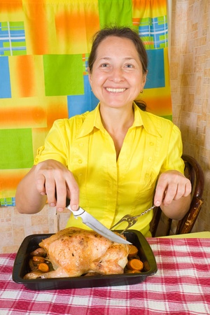 Mature woman with cooked baked chicken on roasting pan in kitchen Stock Photo - 9676180