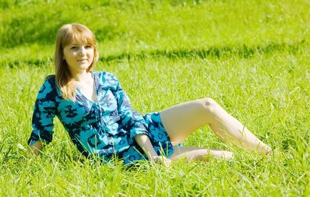teener: Pretty girl in blue dress sitting in meadow grass