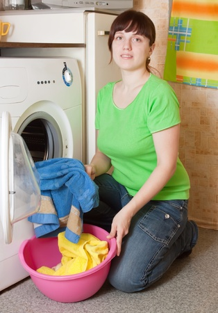 Young woman loading the washing machine in kitchen Stock Photo - 9676214