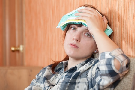 stupes: Suffering girl stupes  towel to her head Stock Photo