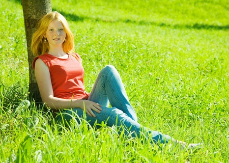 Red-haired teen girl is sitting near tree photo