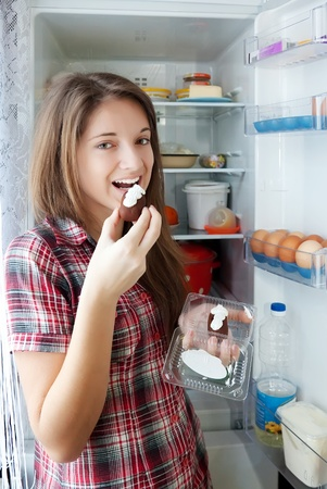 Teenager girl eating  pastry from  fridge  at home photo