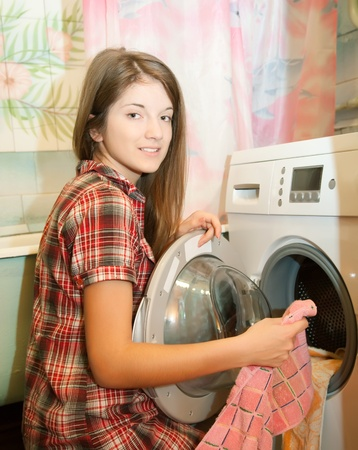domestic chore: Teenager girl doing laundry at her home Stock Photo