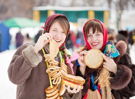 Women in traditional  clothes tasting pancake  during  Shrovetide Stock Photo - 9676348