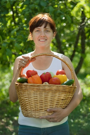 Happy young woman with vegetables harvest in garden photo