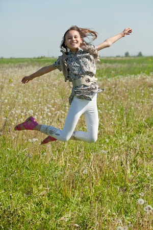 Happy teenager girl jumps at meadow in summer photo