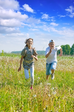 Teen friends running at meadow in summer photo