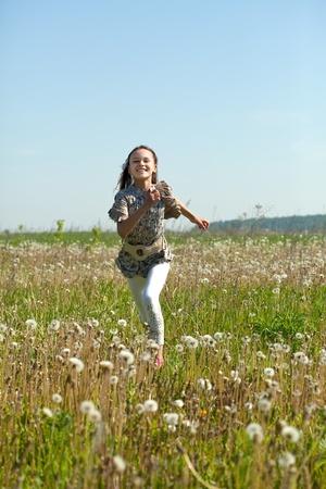teener: Happy teenager girl running at meadow in summer