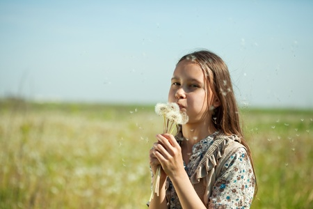 Young girl blowing seeds of dandelion flower photo