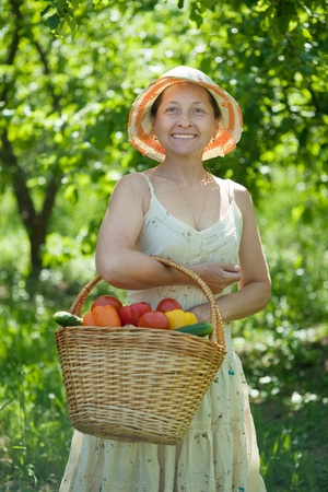 Happy mature woman with basket of harvested vegetables Stock Photo - 9853710