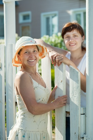 wicket: Two happy women near fence wicket. Selective focus on left woman Stock Photo