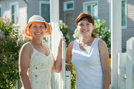 poling: Two happy women near fence wicket  in front of home