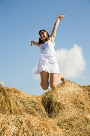 Jumping  country girl over hay in summer photo