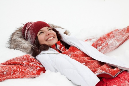 woman lying down: Happy girl lying down on the snow in winter