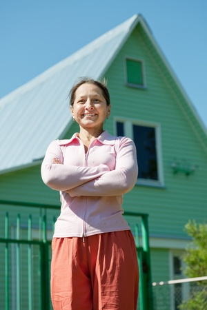 Happy mature woman posing in front of her  home photo