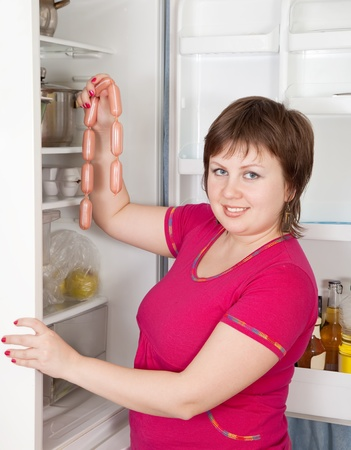woman taking  sausages from refrigerator  at home photo