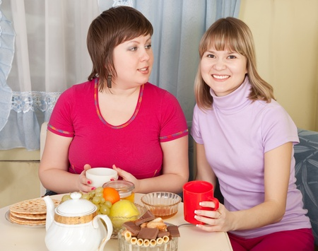 portrait of two girls  drinking tea and gossiping in home photo