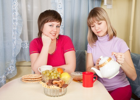 Two smiling women have tea in kitchen Stock Photo - 9854211