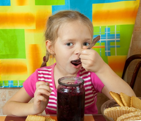 Little girl eating jam from  jar at kitchen Stock Photo - 9854293