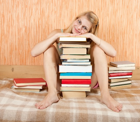 pretty female student with books on sofa at home photo