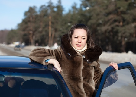 capping: Young woman with her car in winter day Stock Photo