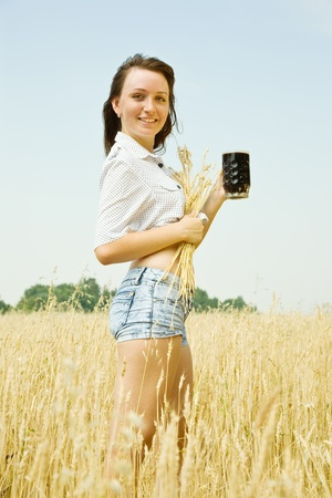 Girl  with quass and wheat ears  at cereals field photo
