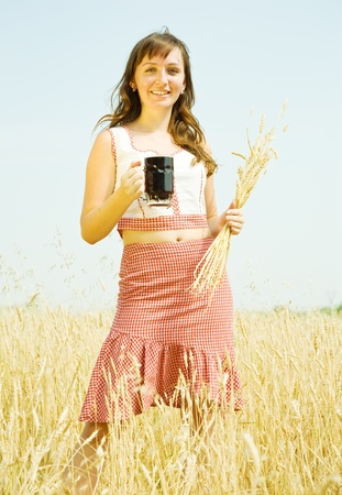 Girl  with kvass at cereals field in summer photo