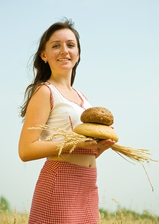 Girl in traditional clothes with bread  at wheat field Stock Photo - 9854336