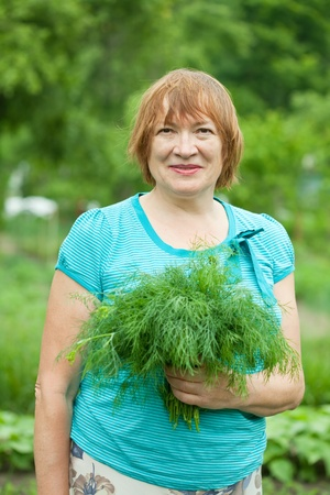 Mature woman with harvested dill in garden Stock Photo - 9854530