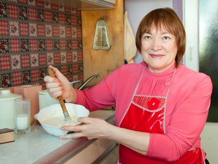 Woman beating dough  in  bowl at her kitchen photo